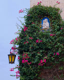 Decorated corner of house, Mdina, Malta. Corner of house decorated with climbing plants with flowers, with antique lantern and sign of Mary and Child Royalty Free Stock Photos