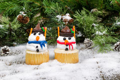 Decorated cupcake snowmen on snowy evergreen background Stock Images