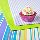 Decorated cupcake on stripy tablecloth Stock Photo