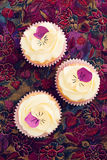 Decorated cupcakes. Cupcakes with buttercream and pansy sugar flowers stock images