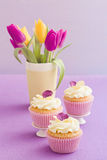 Decorated cupcakes. Cupcakes with buttercream and pansy sugar flowers stock photo