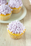 Decorated Cupcakes. Yellow cupcakes decorated with purple pastel icing Stock Photos