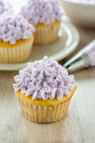 Decorated Cupcakes. Yellow cupcakes decorated with purple pastel icing Stock Photo