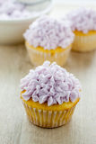 Decorated Cupcakes. Yellow cupcakes decorated with purple pastel icing Stock Image