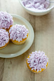 Decorated Cupcakes. Yellow cupcakes decorated with purple pastel icing Royalty Free Stock Photos