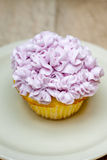 Decorated Cupcakes. Yellow cupcakes decorated with purple pastel icing Royalty Free Stock Images