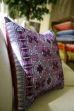 Decorated cushion. Blue and purple decorated cushion on a sofa Royalty Free Stock Image