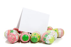 Decorated easter eggs with a blank notecard. A row of decorated pastel easter eggs on a white background with a blank notecard Stock Images
