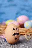 Decorated easter eggs. Closeup of a brown egg with a funny face on a rustic wooden surface and some decorated easter eggs in the background, against a blue Stock Photos