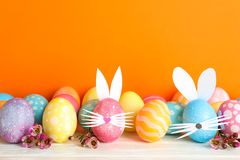 Decorated Easter eggs and cute bunny`s ears on table against color background royalty free stock images