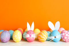 Decorated Easter eggs and cute bunny`s ears on table against color background stock photos