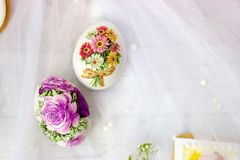 Decorated Easter eggs and flowers on white tulle background; decoupage technique stock image