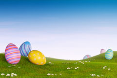 Decorated Easter eggs in a grassy hilly landscape Royalty Free Stock Photos