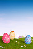 Decorated Easter eggs in a grassy hilly landscape. Decorated Easter eggs lying in the grass in a hilly landscape Royalty Free Stock Photography
