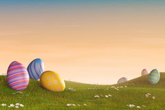 Decorated Easter eggs in a grassy hilly landscape at sunset. Decorated Easter eggs lying in the grass in a hilly landscape at sunset Royalty Free Stock Photography