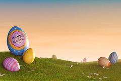 Decorated Easter eggs in a grassy hilly landscape at sunset. Decorated Easter eggs lying in the grass in a hilly landscape at sunset Stock Photo