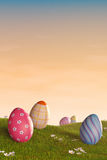 Decorated Easter eggs in a grassy hilly landscape at sunset Stock Photo