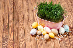Decorated easter eggs, pink bowl with green grass on wooden background. Space for text. Royalty Free Stock Photo