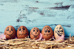 Decorated easter eggs. Some brown eggs with funny faces on a pile of straw, against a blue rustic wooden background with a blank space above them Royalty Free Stock Image