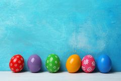 Decorated Easter eggs on table near color wall stock image