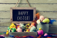 Decorated easter eggs and text happy easter. A wooden-framed chalkboard with the text happy easter hanging on a rustic wooden wall, and a pile of different Royalty Free Stock Images