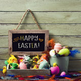 Decorated easter eggs and text happy easter. A wooden-framed chalkboard with the text happy easter hanging on a rustic wooden wall, and a pile of different Stock Photography