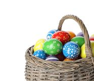 Decorated Easter eggs in wicker basket on white. Background royalty free stock images