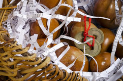 Decorated eggs in basket with Feng Shui coins. Decorated eggs in basket on shredded paper with Feng Shui coins stock photo