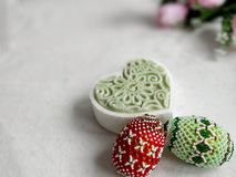 Decorated eggs, green candle shape of heart on natural fabric background. stock images