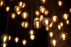 Decorated electric garland for lighting with bulbs warm white and yellow light on a dark background. Blurred background. Bulbs in