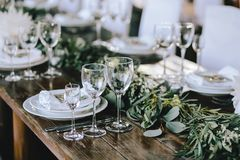 Decorated elegant wooden wedding table in rustic style with eucalyptus and flowers, porcelain plates, glasses, napkins and cutlery. Horizontal stock photos