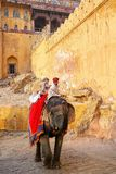 Decorated elephant with tourists going on the cobblestone path t. O Amber Fort near Jaipur, Rajasthan, India. Elephant rides are popular tourist attraction in royalty free stock image