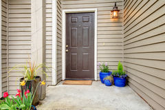 Decorated entrance porch. Open porch with concrete floor, column and entrance brown door. Decorated with hanging latern light and pots with flowers Royalty Free Stock Photography