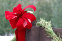 Decorated fence during the christmas holidays. color contrast. Red bow &  pine garland on a fence in December during the Christmas holidays. Snow is on the Royalty Free Stock Photos