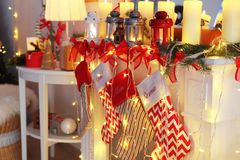 Decorated fireplace with Christmas lanterns, candles and socks. In room royalty free stock photo