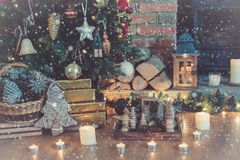 Christmas setting, decorated fireplace, fur tree. Decorated fireplace with woodburner, lit up Christmas tree with baubles and ornaments, lantern, stars and Royalty Free Stock Image