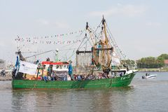 Decorated fishing ship is leaving the harbor Stock Images