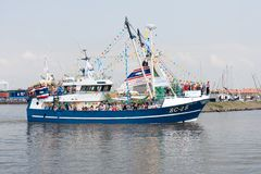 A decorated fishing ship is leaving the harbor Stock Images