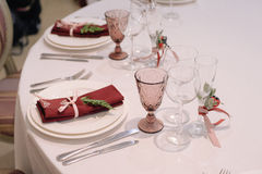 Decorated with flowers boutonniere glasses and settings. Decorated with flowers boutonniere wine and champagne glasses and settings with decorated napkin Royalty Free Stock Image