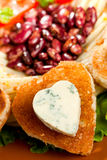 Decorated fried bread and blue cheese in the shape of a heart. Stock Photo
