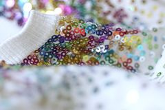 Fashionable spangly garment. Closeup of white garment decorated with countless colourful metallic sequins. A woman would look stunning in such a fashionable royalty free stock photos