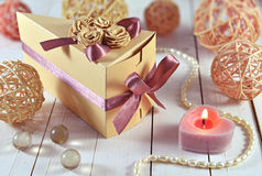 Decorated gift box with candle and romantic trinkets. Still life with gift in the triangle decorated box with candle and jewelry on wooden planks Stock Image