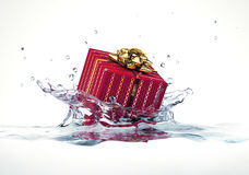 Decorated gift falling into water splashing. At wh Royalty Free Stock Image