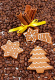 Decorated gingerbread and cinnamon sticks on coffee grains, christmas time Royalty Free Stock Image