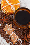 Decorated gingerbread, cup of coffee and grains, spices, christmas time Royalty Free Stock Photo
