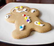 Decorated gingerbread man on white plate Royalty Free Stock Image