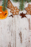 Decorated gingerbread, spruce branches, spices on old wooden background, christmas decoration Stock Photography