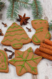 Decorated gingerbread, spruce branches, spices on old wooden background, christmas decoration Royalty Free Stock Photo