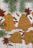 Decorated gingerbread, spruce branches, spices on old wooden background, christmas decoration Stock Photos