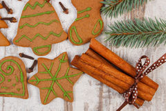 Decorated gingerbread, spruce branches, spices on old wooden background Royalty Free Stock Photo